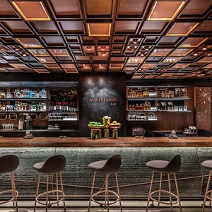 The custom walnut ceiling frames this bar perfectly
