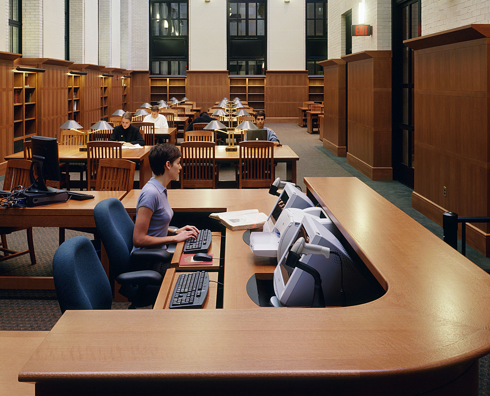 The circulation desk and the furniture in this space make for a warm and welcoming environment. Even with the high arched-glass ceilings, the warm wood keeps everything to scale.