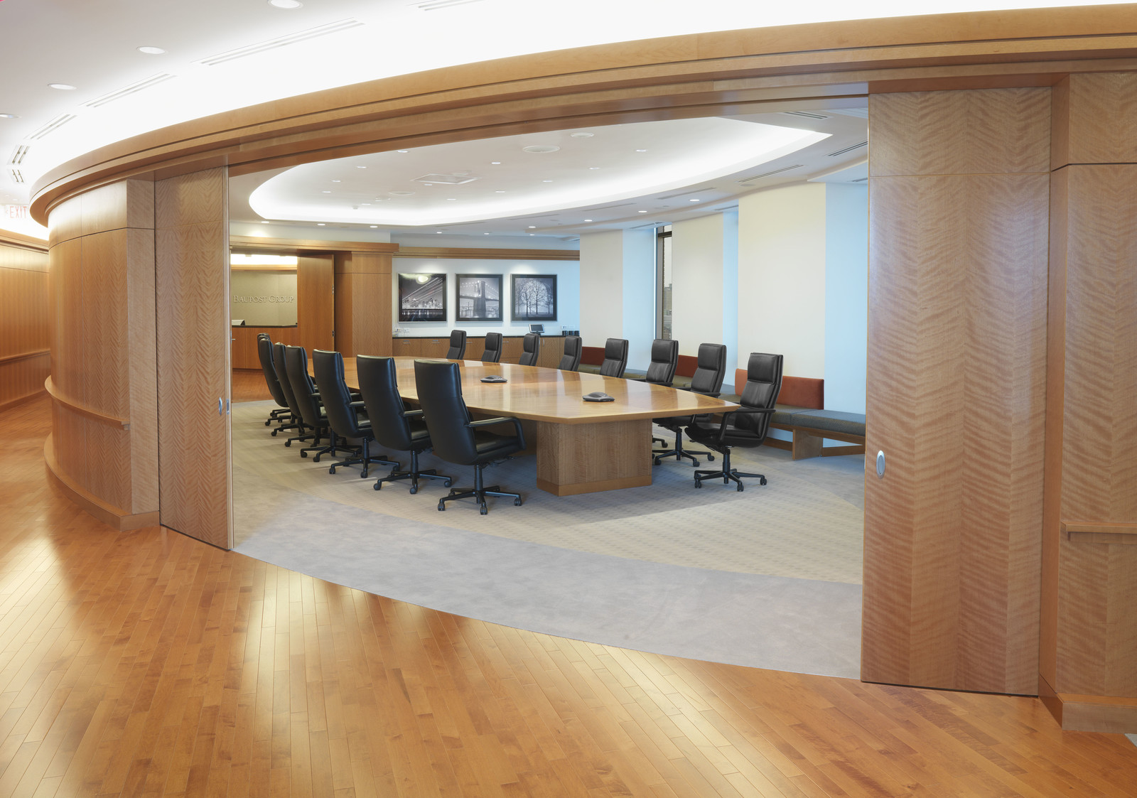 Curved entrance and wall paneling top off a gorgeous custom wood conference table.